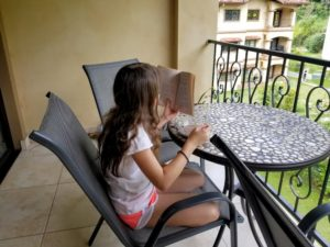My Homeschooling Review After One Interesting Year - Faith reading on the balcony