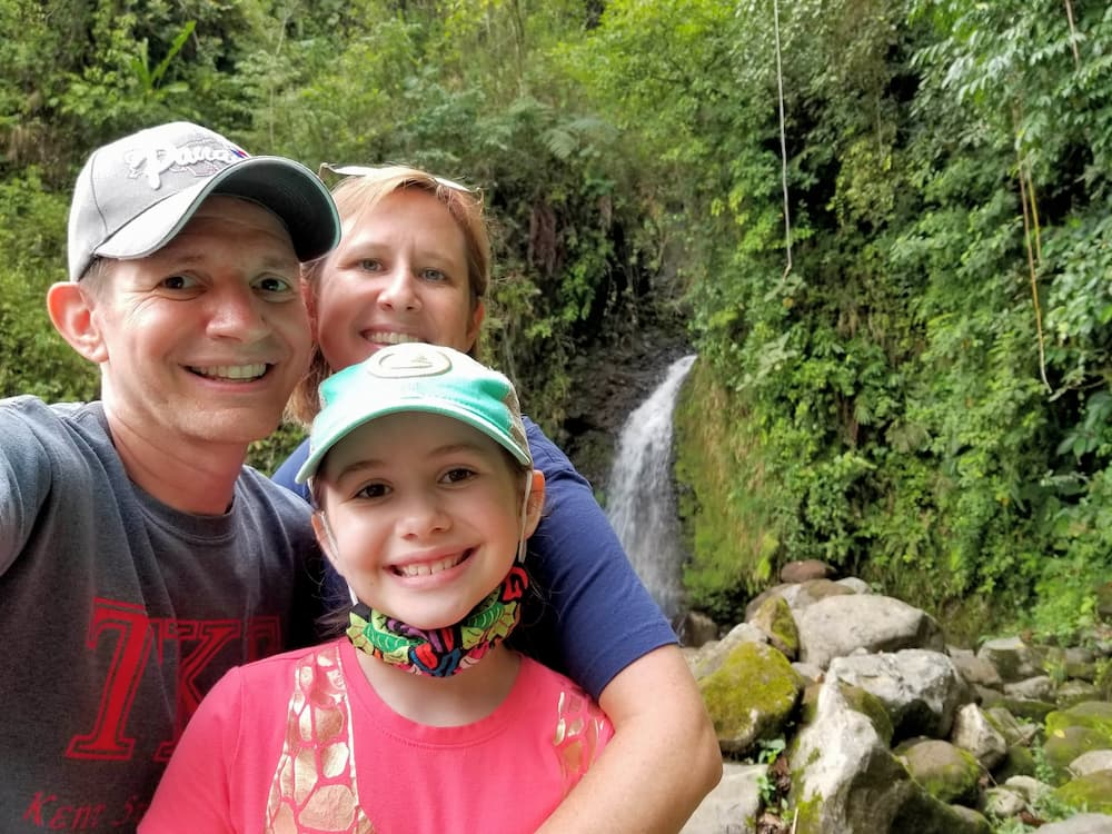 Designing Our New Life – The Power of Early Retirement - Jim, Lisa, and Faith in front of a waterfall
